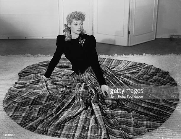 American actress Lucille Ball wearing a long dress with a tartan skirt and a large butterfly brooch.