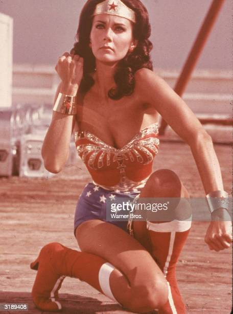 American actress Lynda Carter kneels and bares her forearm in a scene from the television series 'Wonder Woman' in which she plays the title...