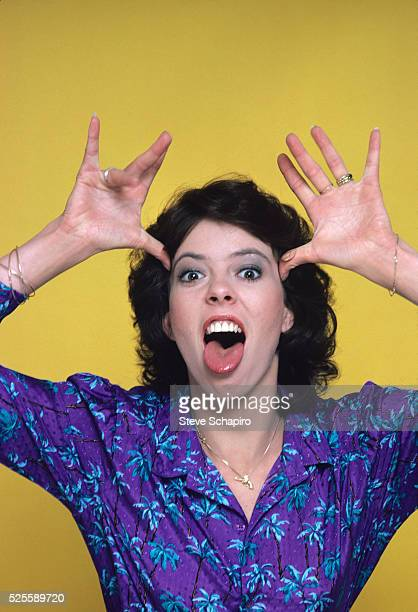 American actress Mackenzie Phillips poking her tongue out and gesturing with her hands in a studio portrait against a yellow background circa 1980