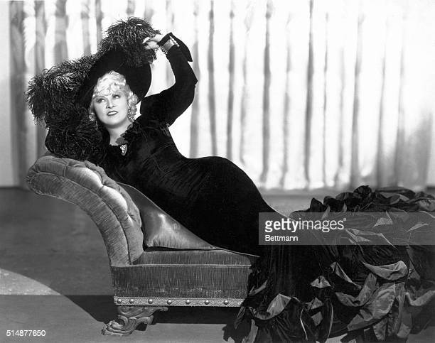 Mae West in her typical long black slinky gown with large feathered picture hat lying in chaise Undated Photograph