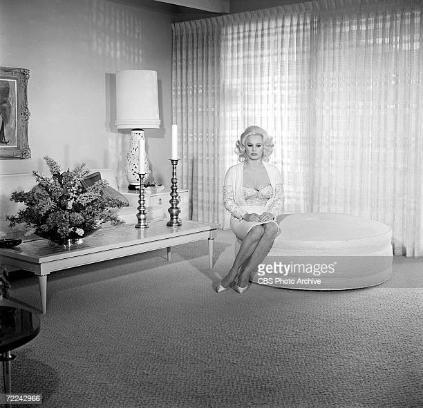 American actress Mamie van Doren sits on a large round ottoman in her living room during an episode of the CBS celbrity interview program 'Person to...