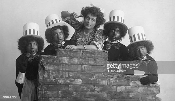 American actress Marie George stars in a production of 'Sindbad the Sailor' circa 1910 Her costars are wearing 'blackface' and top hats