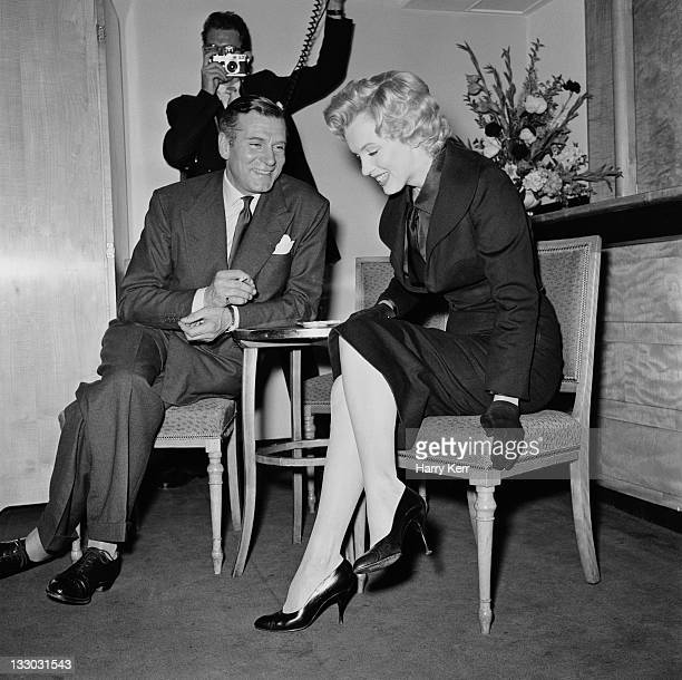 American actress Marilyn Monroe and English actor and director Laurence Olivier at a press conference at the Savoy Hotel London July 1956 Monroe is...