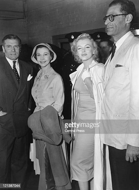 American actress Marilyn Monroe and her husband playwright Arthur Miller are met at London Airport by Sir Laurence Olivier and his wife actress...
