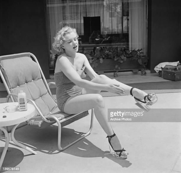 American actress Marilyn Monroe applies Nivea lotion to her legs circa 1951