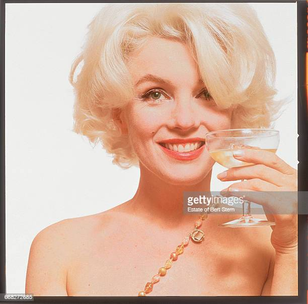 American actress Marilyn Monroe holding a glass of champagne Beverly Hills California June 1962 The two sessions for the photoshoot took place in...