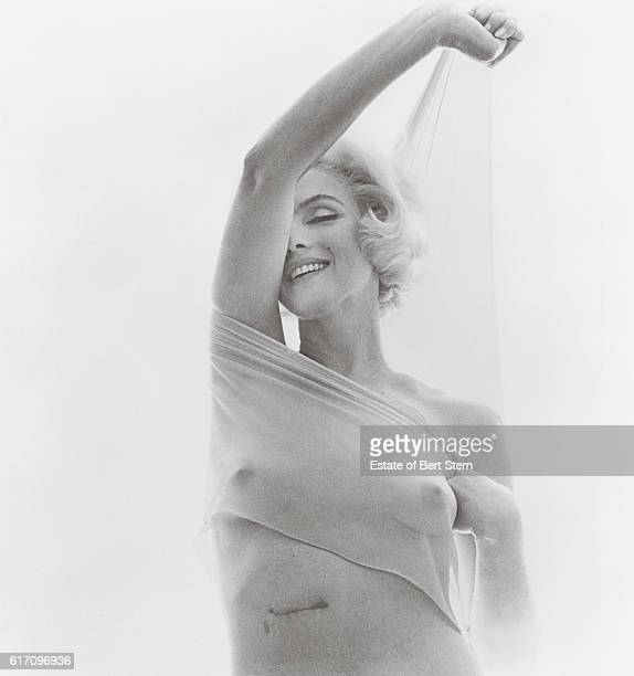 American actress Marilyn Monroe holding a sheer scarf Beverly Hills California June 1962 The scar from a gallbladder operation is visible on her...