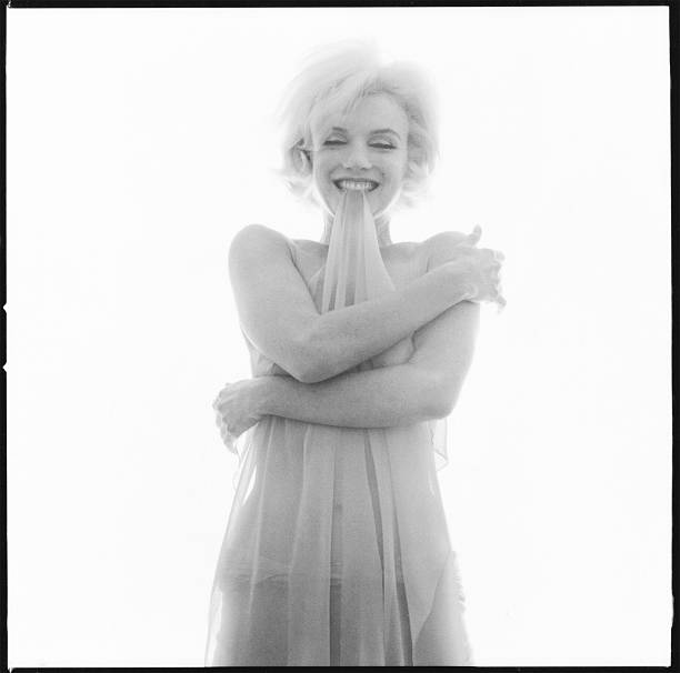 American actress Marilyn Monroe holding a sheer scarf in her teeth Beverly Hills California June 1962 The two sessions for the photoshoot took place...