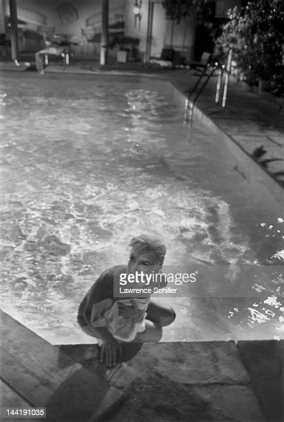 APPLY American actress Marilyn Monroe holds a towel in front of her as she climbs topless out of a pool during the filming of 'Something's Got to...