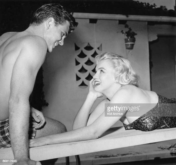 American actress Marilyn Monroe in a bathing suit and lying on her stomach looks up to flirt with a friend at the pool Hollywood California 1950
