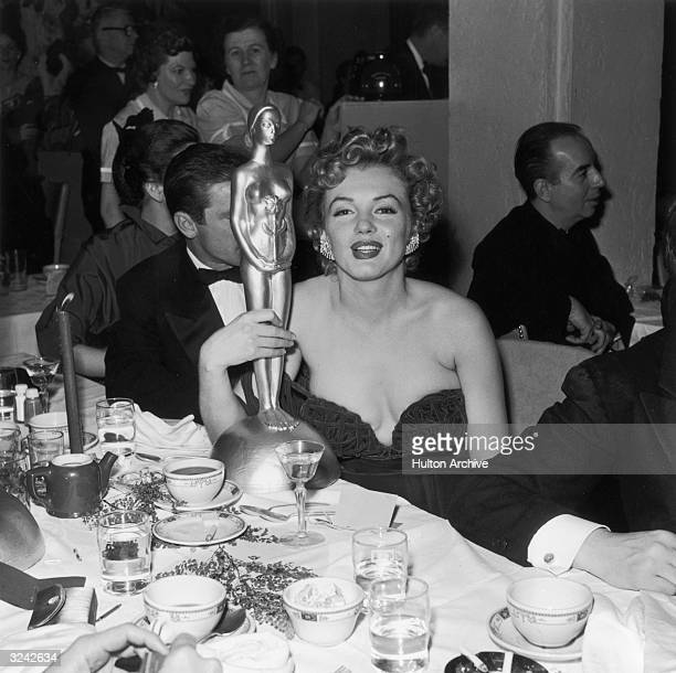 American actress Marilyn Monroe in a lowcut strapless velvet dress poses with her 'Henrietta' statuette at the Foreign Press Association of...