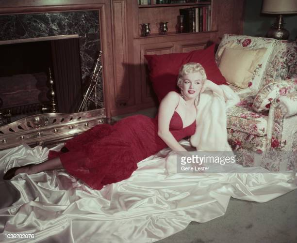 American actress Marilyn Monroe in a red brocade evening gown reclining on white satin with her head resting on a white fur coat 1955