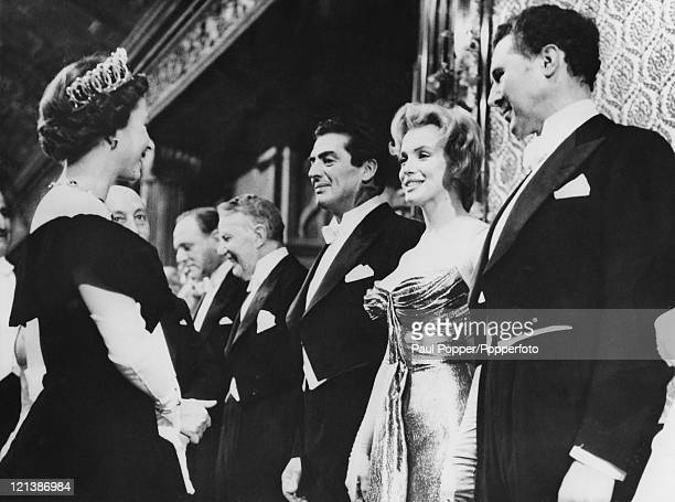 American actress Marilyn Monroe is presented to Queen Elizabeth II at the royal charity performance of 'The Battle of the River Plate' at the Empire...