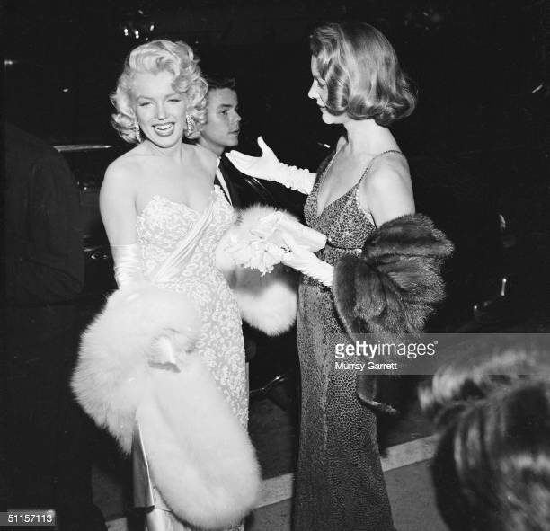 American actress Marilyn Monroe laughs with fellow actress Lauren Bacall at the premiere of Jean Negulesco's film 'How to Marry a Millionaire' in...