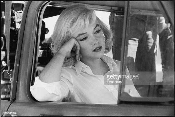 American actress Marilyn Monroe leans out of the open window frame of a car on the set of 'The Misfits' directed by John Huston Nevada 1960