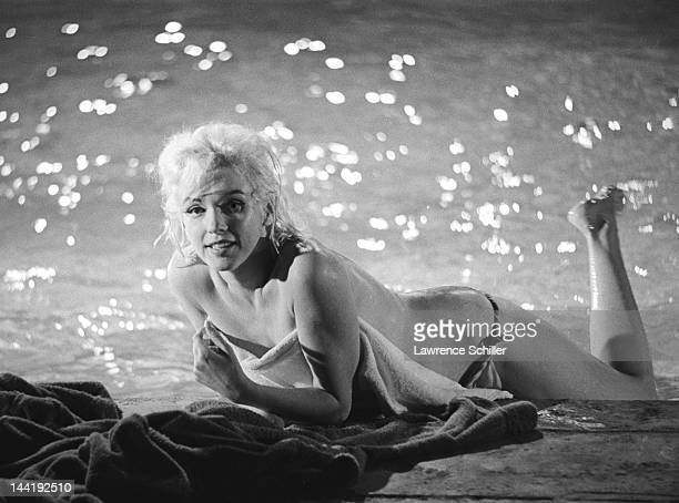 APPLY American actress Marilyn Monroe lies topless on the deck of a pool during the filming of 'Something's Got to Give' Los Angeles California May...