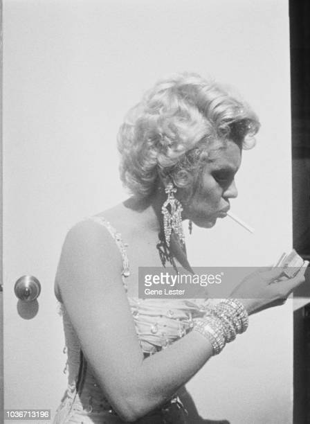 American actress Marilyn Monroe lighting a cigarette on the set of 'There's No Business Like Show Business' directed by Walter Lang at the 20th...
