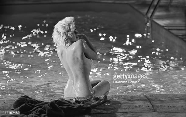 APPLY American actress Marilyn Monroe looks over her shoulder as she sits topless on the deck of a pool during the filming of 'Something's Got to...