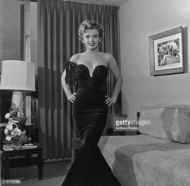 American actress Marilyn Monroe posing in an evening dress with her hands on her hips circa 1955