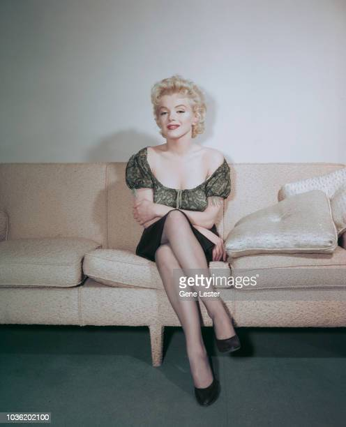 American actress Marilyn Monroe posing on a sofa during a press call to publicise her latest film Joshua Logan's 'Bus Stop' 1956