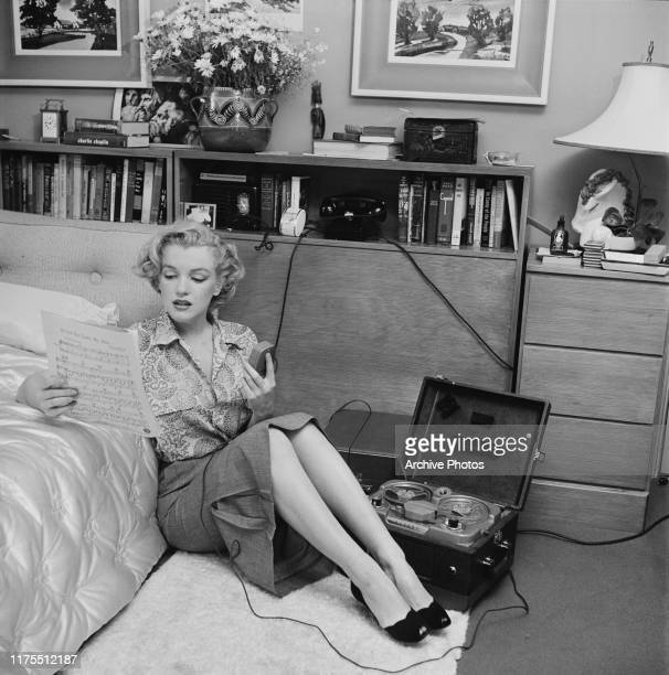 American actress Marilyn Monroe reading sheet music while sitting on a bedroom floor with a tape player on the side US circa 1950