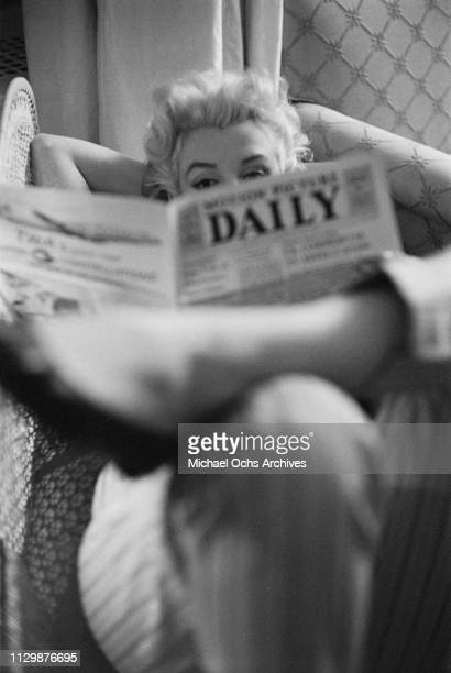 American actress Marilyn Monroe reads the newspaper 'Motion Picture Daily' as she relaxes on a couch in her hotel room at the Ambassador Hotel in New...