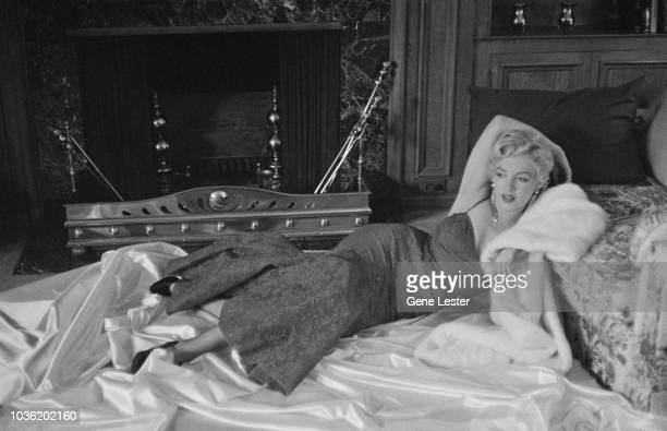 American actress Marilyn Monroe reclining on white satin in a brocade evening gown 1955
