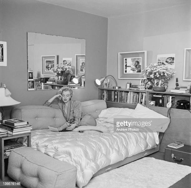 American actress Marilyn Monroe relaxes on a sofa bed, circa 1951. The book she is reading is 'The Poetry and Prose of Heinrich Heine'.