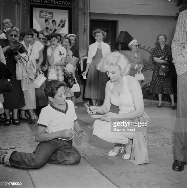 American actress Marilyn Monroe signs an autograph for a fan outside Grauman's Chinese Theatre in Hollywood, California, 26th June 1953. Monroe is at...