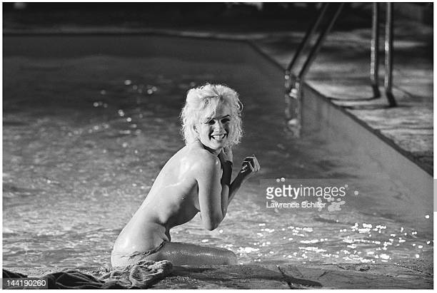 APPLY American actress Marilyn Monroe sits topless on the deck of a pool during the filming of 'Something's Got to Give' Los Angeles California May...