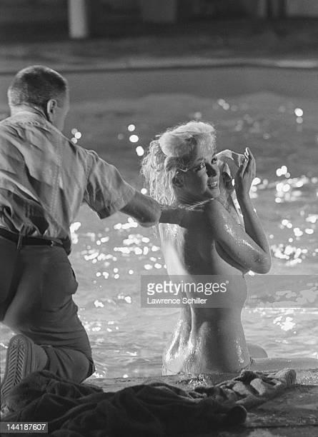 American actress Marilyn Monroe sits topless with her makeup artist Allan Snyder during the filming of a pool scene from 'Something's Got to Give'...