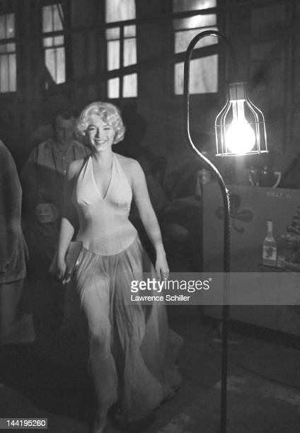 American actress Marilyn Monroe smiles as she walks with a script during the filming of their movie 'Let's Make Love' Los Angeles California April...