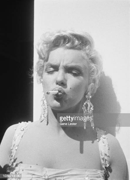 American actress Marilyn Monroe smokes a cigarette on the set of 'There's No Business Like Show Business' directed by Walter Lang at the 20th Century...