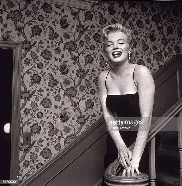 American actress Marilyn Monroe stands in a staircase alongside a wall with a floral-motif pattern, late 1950s. She wears a black cocktail dress and...