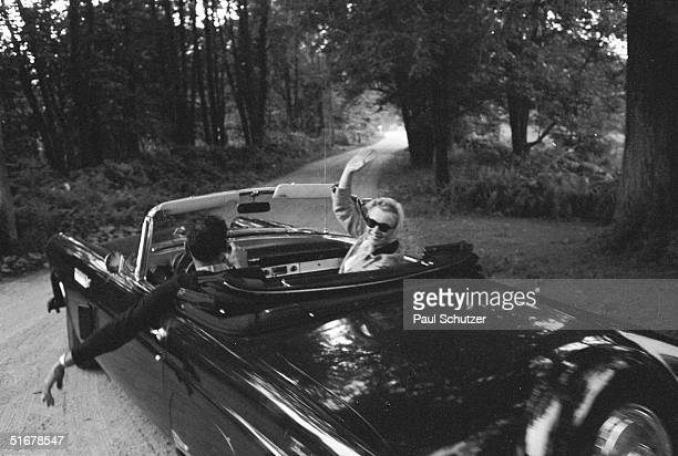 American actress Marilyn Monroe waves as she and her husband, American playwright Arthur Miller, go for a drive in Miller's convertible car, Roxbury,...