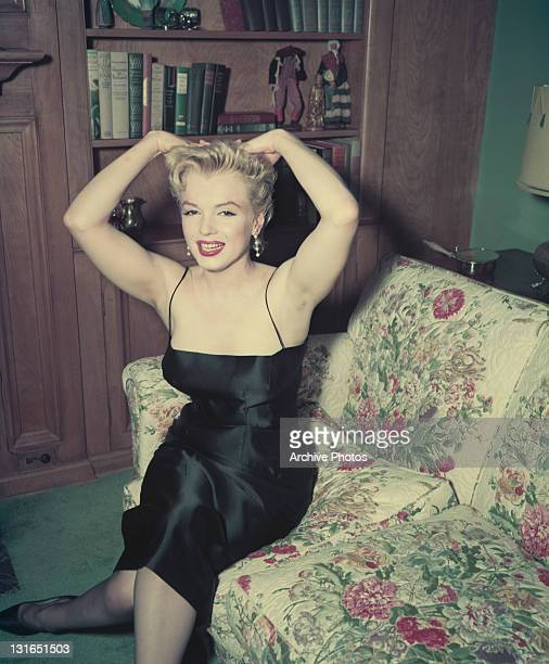 American actress Marilyn Monroe wearing a black satin dress 1956