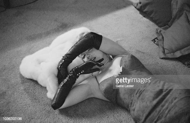 American actress Marilyn Monroe wearing a brocade evening gown and black evening gloves and lying with her head resting on a white fur coat 1955