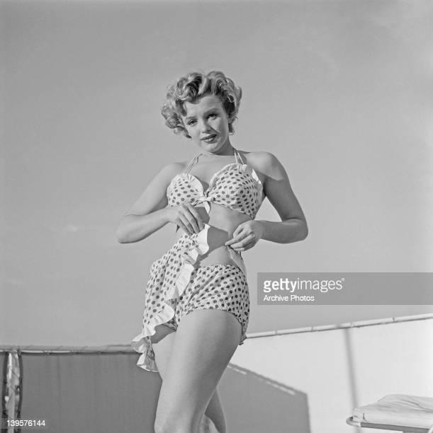 American actress Marilyn Monroe wearing a polka dot bikini with a matching wraparound miniskirt circa 1951
