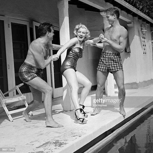 American actress Marilyn Monroe wearing heels and a bathing suit plays around with two male friends at the pool Hollywood California 1950