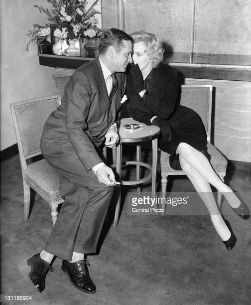 American actress Marilyn Monroe whispers to English actor and director Laurence Olivier during a press conference at the Savoy Hotel London 16th July...