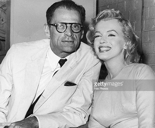 American actress Marilyn Monroe with her husband playwright Arthur Miller at London Airport 14th July 1956 Monroe is in London to begin filming 'The...