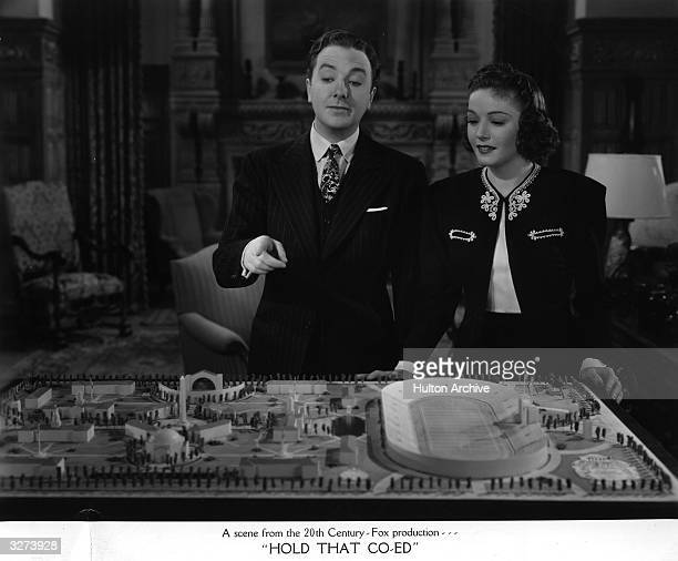 American actress Marjorie Weaver is shown the plans for a stadium by Jack Haley in a scene from the film 'Hold That Coed' directed by George Marshall...