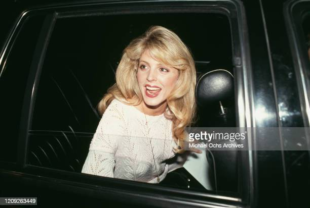 American actress Marla Maples, wearing a white knitted sweater, sitting in the rear seat of a car, smiles as she looks through the open window, circa...