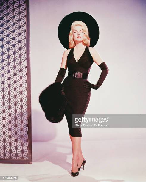 American actress Martha Hyer wearing a black cocktail dress and widebrimmed hat circa 1955