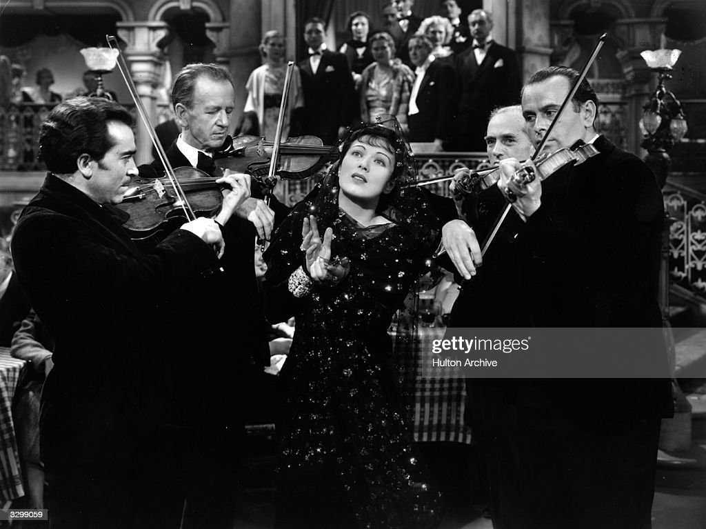 American actress Mary Ellis accompanies a group of violinists with a