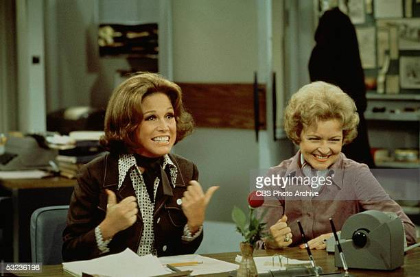 American actress Mary Tyler Moore gives a 'thumbs up' sign as she sits at her desk with Betty White in a scene from 'The Mary Tyler Moore Show' Los...