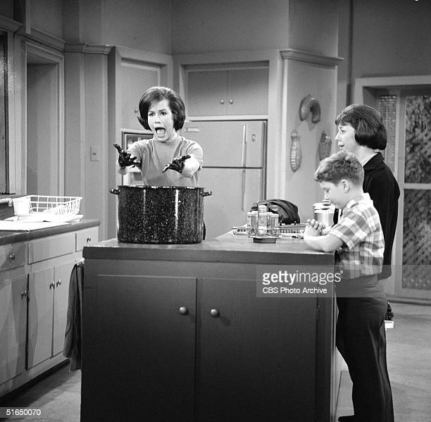 American actress Mary Tyler Moore reacts to getting dye all over her hands as American actors Larry Mathews and Ann Morgan Guilbert look on in a...
