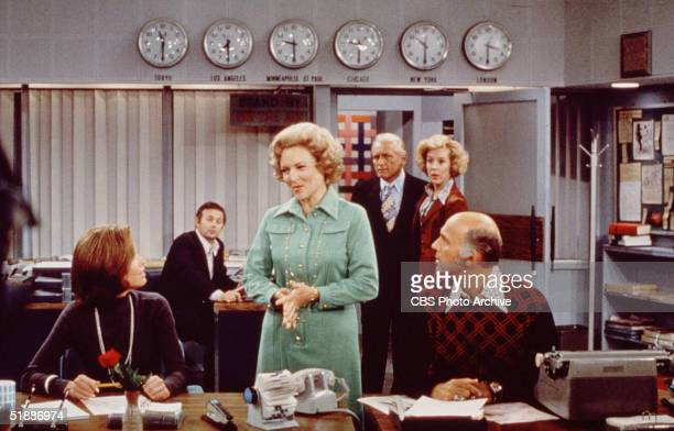 American actress Mary Tyler Moore sits at her desk as Betty White talks to her and Gavin MacLeod listens in a scene from 'The Mary Tyler Moore Show'...