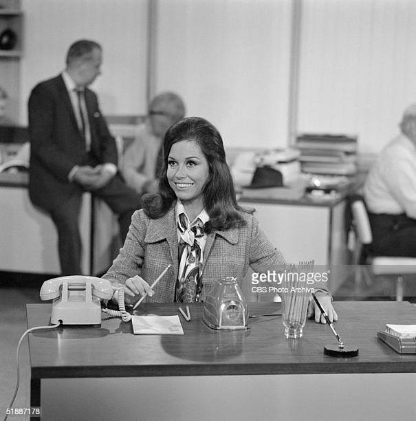 American actress Mary Tyler Moore sits at her new desk and sharpens pencils in an electric sharpener after being hired in the newsroom of television...