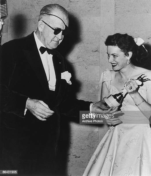 American actress Maureen O'Hara presents film director John Ford with a costumers' award for directorial achievement circa 1955